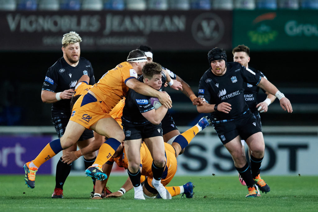 Huw Jones of Glasgow Warriors is tackled by Montpellier players
